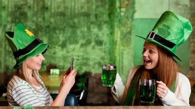 Heureux amies célébrant st. patrick's day avec smartphone et boissons