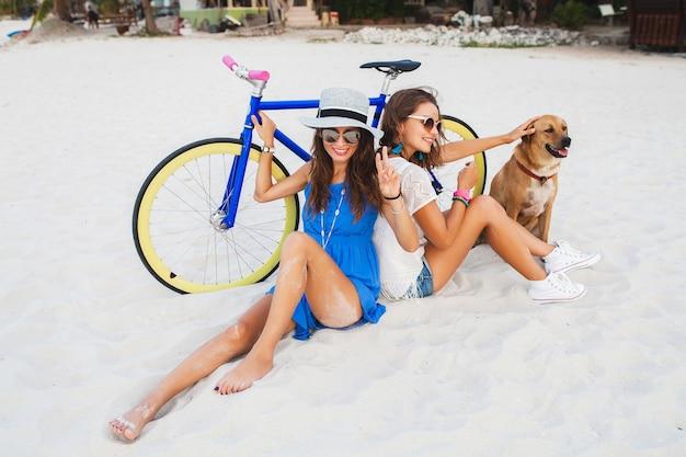 Heureux amies s'amusant sur la plage tropicale, les femmes voyageant en vacances en thaïlande à vélo