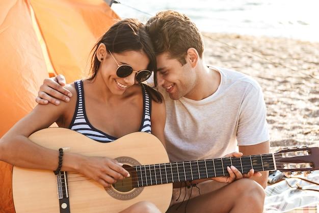 Heureux amis aimant couple en plein air sur la plage assis tout en jouant à la guitare