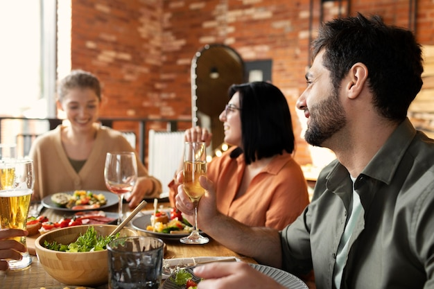 Heureux amis assis à table coup moyen