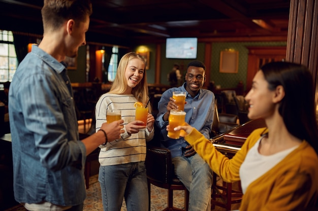 Heureux amis avec de la bière porter un toast au comptoir du bar