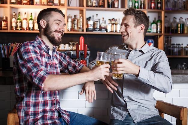 Heureux amis, boire de la bière au comptoir au pub