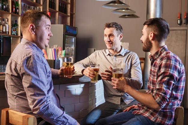 Heureux amis buvant de la bière au comptoir dans un pub