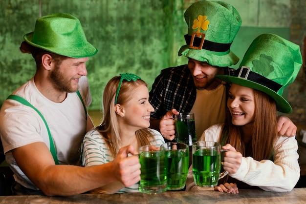 Heureux amis célébrant ensemble st. le jour de patrick avec des boissons