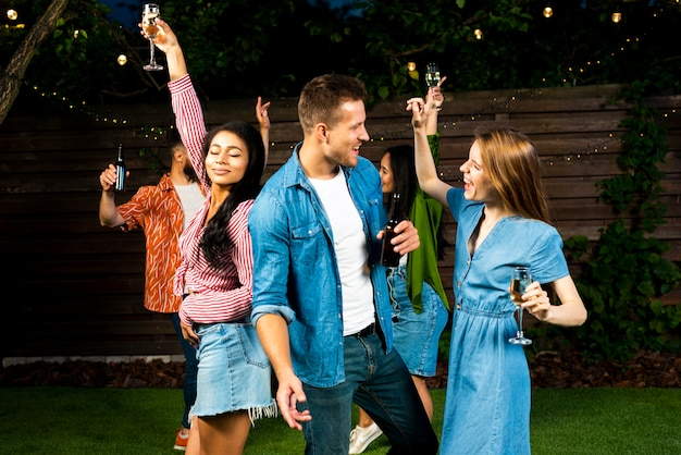 Heureux amis danser ensemble avec des boissons
