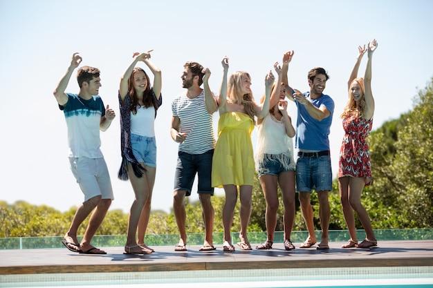 Heureux amis danser près de la piscine