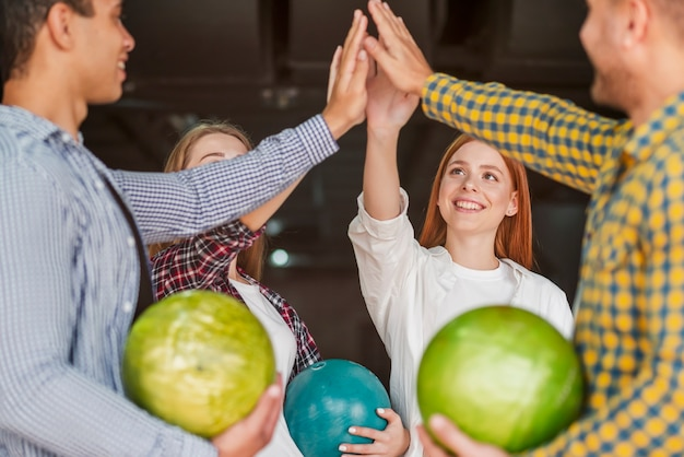 Heureux amis debout dans un club de bowling
