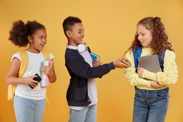 Heureux amis de l'école tenant des fournitures scolaires