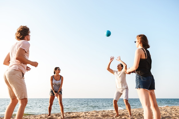 Heureux amis à l'extérieur sur la plage jouer au volley-ball en s'amusant