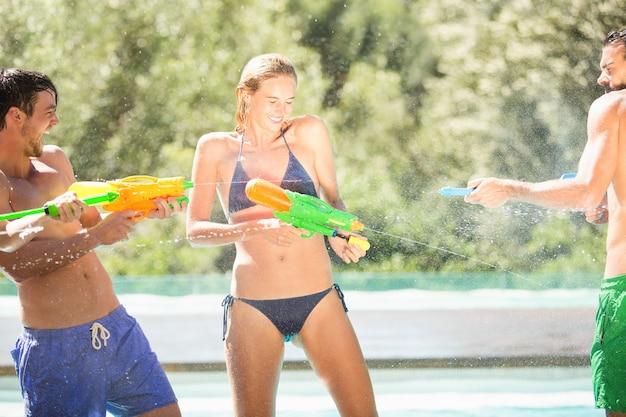 Heureux amis faisant la bataille de pistolet à eau