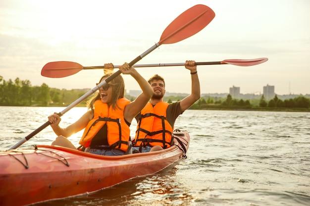 Heureux amis faisant du kayak sur la rivière avec coucher de soleil en arrière-plan