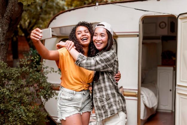 Heureux amis féminins prenant des photos à l'extérieur