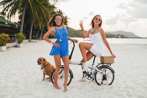 Heureux amis féminins s'amusant sur la plage tropicale