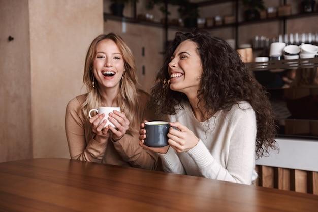 Un heureux amis de filles assis dans un café en train de parler entre eux en buvant du thé ou du café