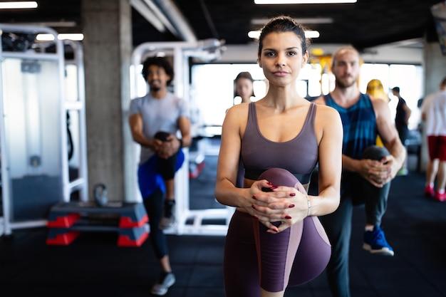 Heureux amis en forme faisant de l'exercice, s'entraînant dans une salle de sport pour rester en bonne santé ensemble