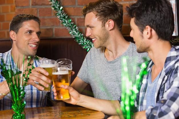 Heureux amis grillage avec des pintes de bière le jour de patricks