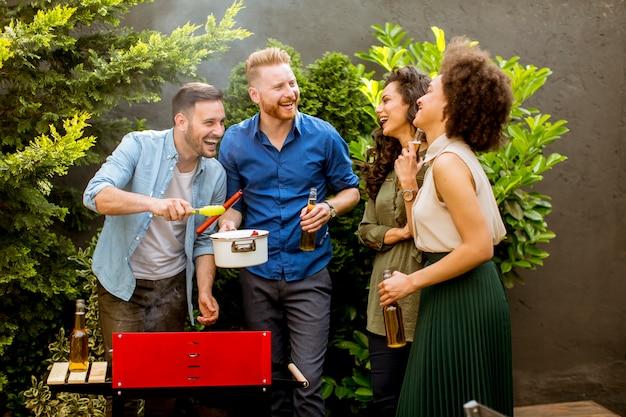 Heureux amis griller des aliments et profiter d'un barbecue en plein air