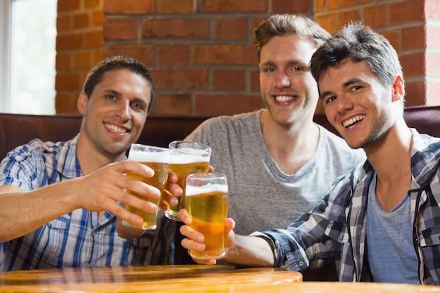 Heureux amis griller avec des pintes de bière dans un bar