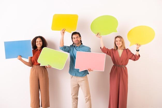 Heureux amis interculturels en tenue décontractée tenant des bulles de papier vierges colorées où vous pouvez écrire vos notes ou vos messages