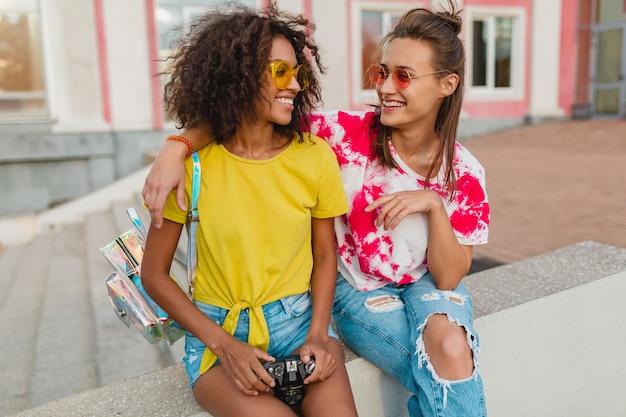 Heureux Amis De Jeunes Filles Souriant Assis Dans La Rue Avec Appareil Photo, Les Femmes S'amusant Ensemble Photo gratuit