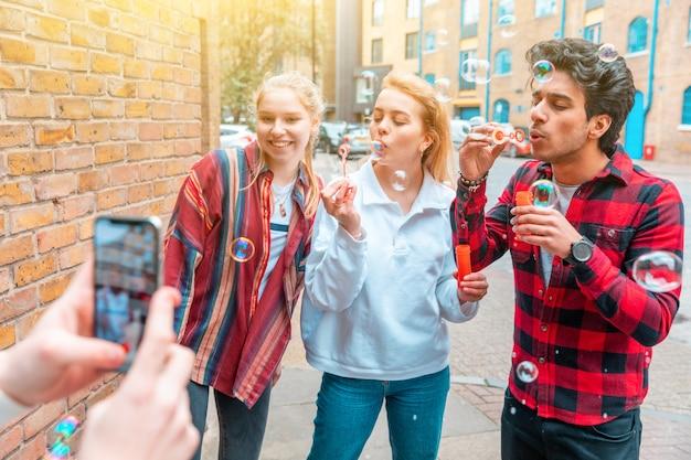 Heureux amis jouant ensemble avec des bulles de savon