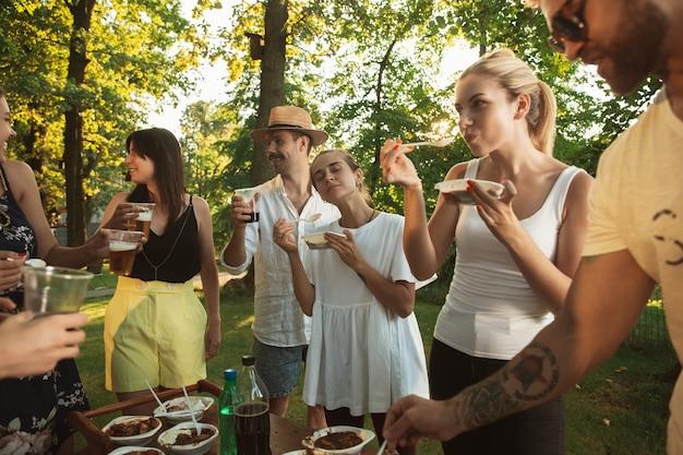 Heureux amis manger et boire des bières au dîner barbecue au coucher du soleil