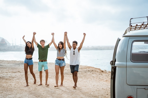 Heureux amis marchant sur la plage et se lèvent les mains