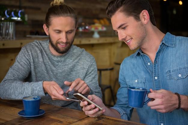 Heureux amis masculins utilisant un téléphone intelligent à table dans un café