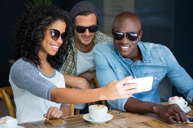 Heureux amis multiethniques portant des lunettes de soleil tout en prenant selfie dans un café