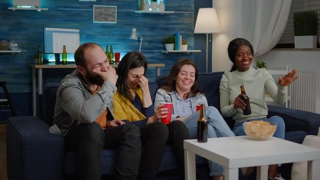Heureux amis multiethniques souriant ensemble assis devant la télévision en regardant drôle venir...