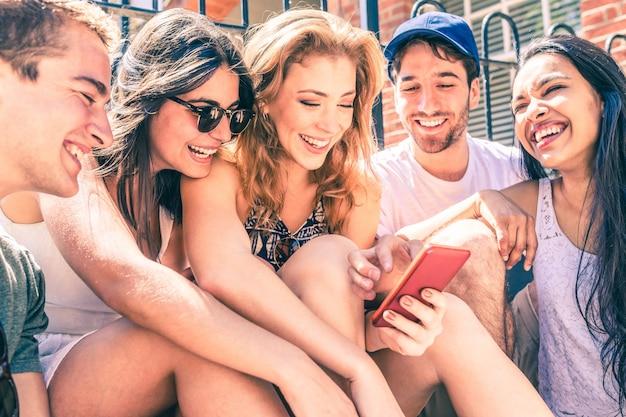 Heureux amis multiraciales s'amusant avec un smartphone