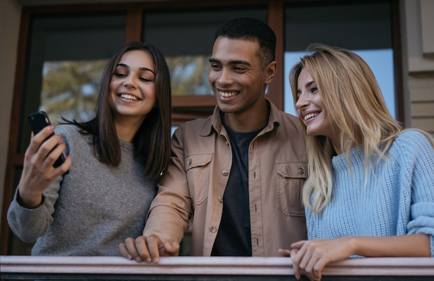 Heureux amis multiraciaux hipster utilisant un smartphone, communiquant ensemble, regardant des vidéos
