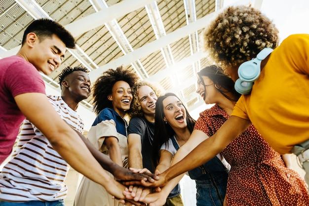 Heureux amis multiraciaux avec les mains dans la pile