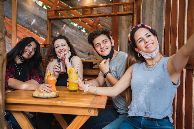 Heureux amis portant des masques et dégustant des boissons aux fruits.