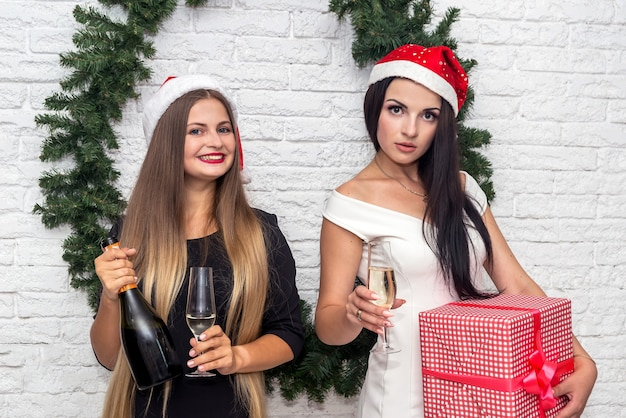 Heureux amis posant avec champagne et coffret cadeau
