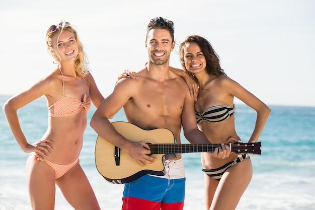 Heureux amis posant et jouant de la guitare sur la plage