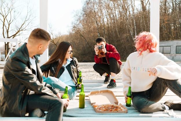 Heureux amis prenant des photos et ayant la fête en plein air