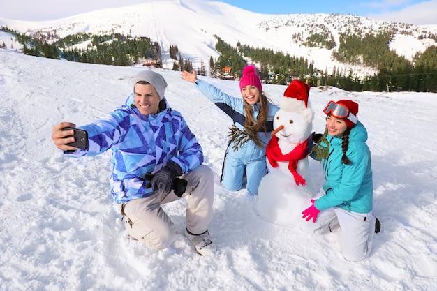 Heureux amis prenant selfie avec bonhomme de neige à la station de ski. vacances d'hiver