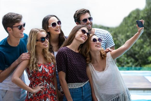 Heureux amis prenant un selfie près de la piscine