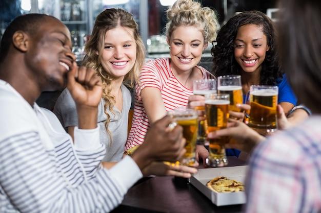 Heureux amis prenant un verre et une pizza