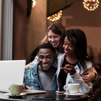 Heureux amis regardant un ordinateur portable à l'intérieur