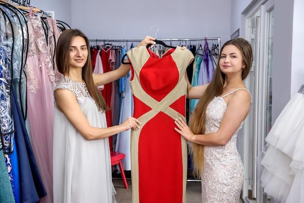 Heureux amis regardant la robe dans le magasin de vêtements