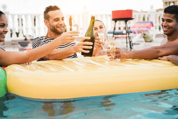 Heureux amis s'amusant à applaudir avec du champagne à l'intérieur de la piscine pendant les vacances d'été - l'accent principal sur le visage de l'homme central