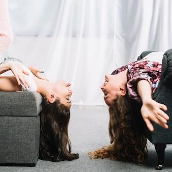 Heureux amis s'appuyant sur une chaise avec la tête baissée