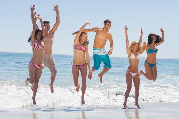 Heureux amis sautant sur la plage
