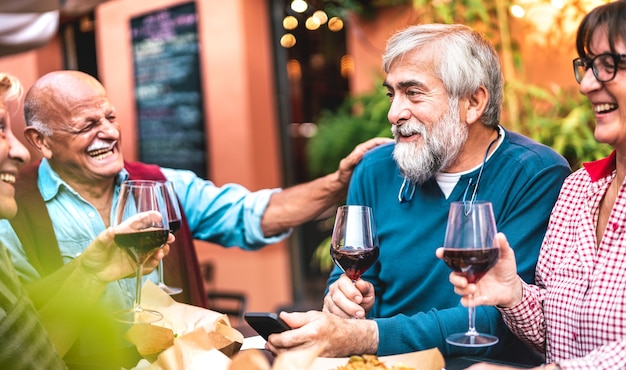 Heureux amis seniors s'amusant à boire du vin rouge au dîner