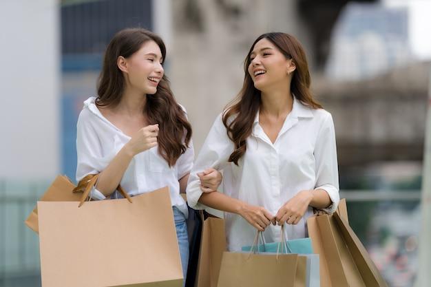 Heureux amis shopping, deux jeunes femmes tiennent des sacs à provisions