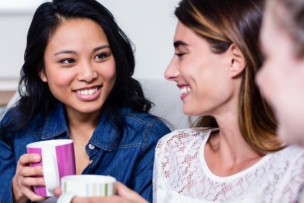 Heureux amis avec une tasse de café assis sur un canapé