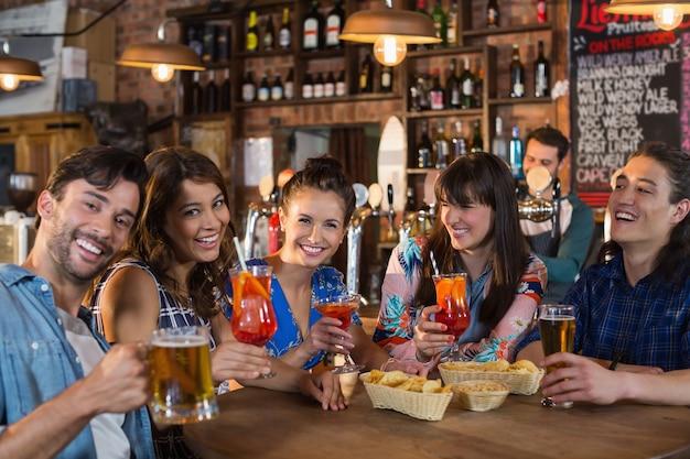 Heureux amis tenant des boissons à table