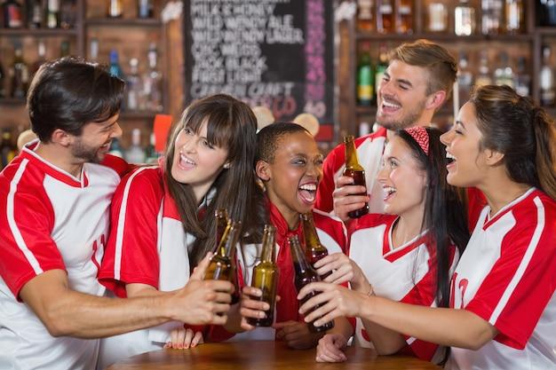Heureux amis tenant des bouteilles de bière